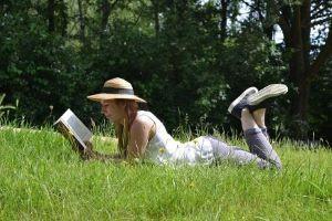 vrouw leest boek al liggend in het gras